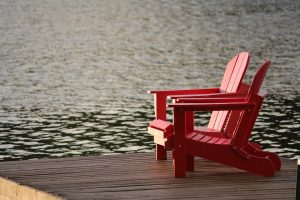 Two red chairs on a dock. The picture gives a sense of tranquility, which you will get if you mover to some of the best US cities to retire.