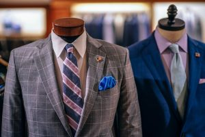 A close up of two different suits in a store. One is grey, and another one is dark blue.