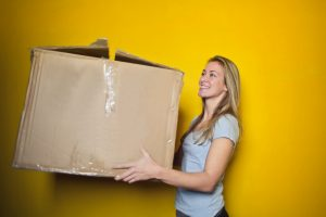 A blonde woman smiling and holding a big cardboard box in front of a yellow surface.