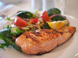 A close up of a piece of salmon on the plate with a lot of green vegetables and a few pieces of tomato.