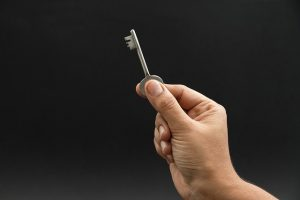 Close up of a hand holding a key.
