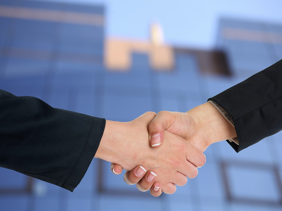 People shaking hands after hiring a moving broker.