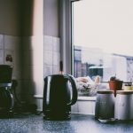 A kettler, and jars in front of the window.