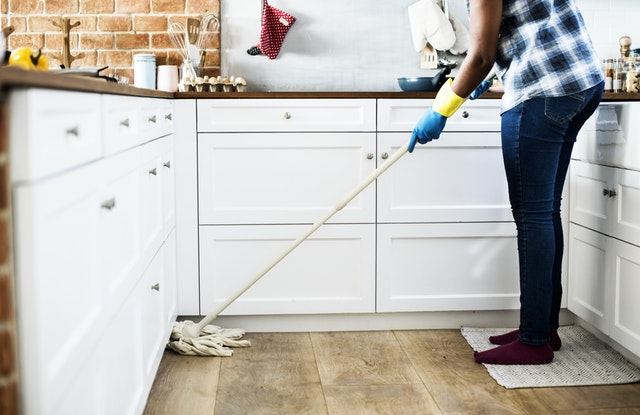 a lady cleaning the kitchen, an example of how you should clean your house after relocation