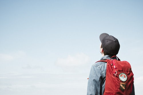 a student with a red backpack staring at the sky