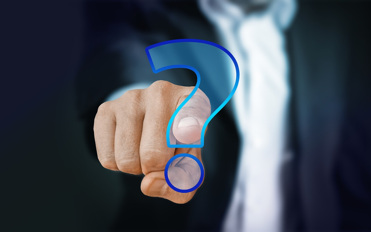 Hand pointing at question mark