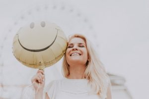 A woman holding a smiley baloon