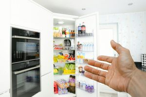 A hand showing to an opened fridge
