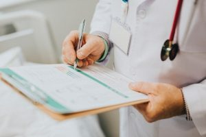 A doctor writing a medical report. If you're thinking of moving while injured, consult your doctor first.