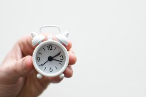 person holding white mini bell alarmclock