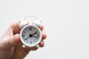 person holding white mini bell alarmclock