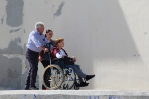 two people pushing a woman in a wheelchair