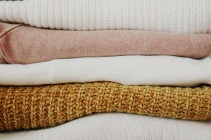 a pile of sweaters in white, brown and pink color