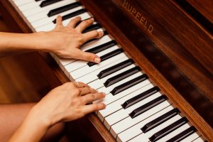a person`s hands playing the piano