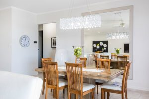 mirrors are some of the most likely items to get damaged during a move. A dining room with a dining table, four chairs and a large mirror and a chandelier