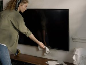 a woman dusting off a large black led TV