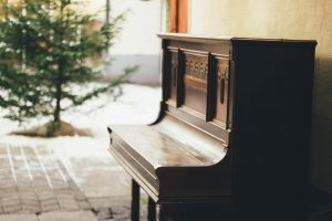 avoid moving injuries by hiring piano movers. a brown closed piano standing in front of the house