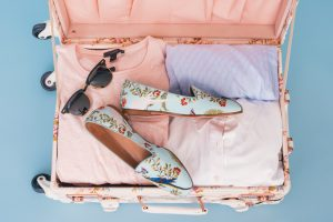 packing wardrobe for moving by using a pink suitcase