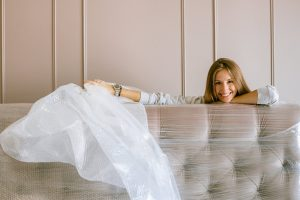 a woman smiling behind a headboard