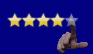 a close up photo of a finger pointing to a five star review