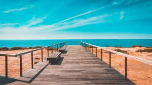 a boardwalk to the ocean photographed during the day