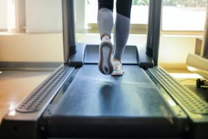 a close up photo of runner`s legs on a treadmill
