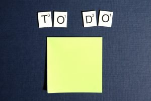 a to-do list on a yellow post it paper on a black surface
