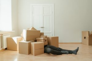 a man lying below several moving boxes during the day in an empty room
