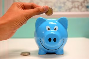a person holding a coin over a blue piggy bank