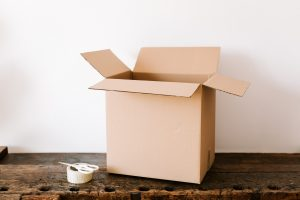 an open moving box, a tape and scissors next to it