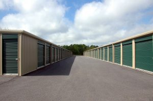 storage units with green doors photographed outside during the day