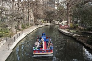 the Riverwalk in San Antonio, people riding in a river barge