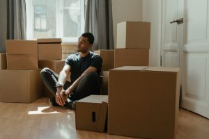 a man sitting calmly amidst the moving boxes
