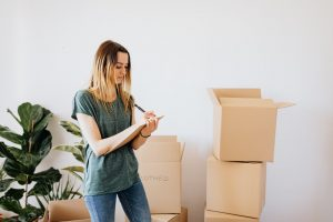 before moving to scottsdale AZ make sure to declutter all of your items. a woman standing in front of moving boxes, taking notes in her notebook
