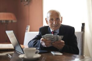 A happy business owner counting his profit fter indroducing an employee reward system.