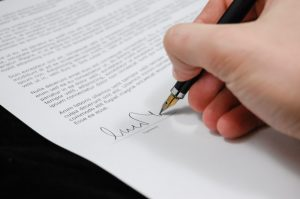 a person holding a pen signing a contract