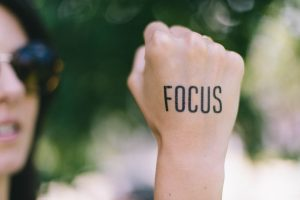 "Woman holding up a fist with the word ""focus"" sharpied on."
