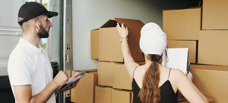 Man and woman preparing boxes for transport.