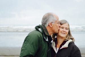 an elderly man kissing a woman on the cheek