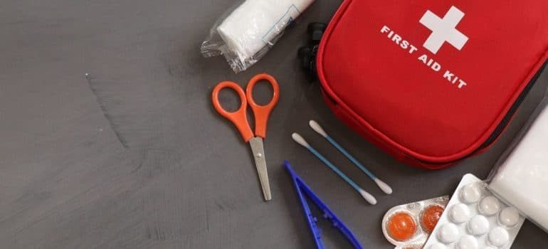 a first aid kit with scissors, q-tips and a bandage near it