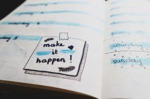A notebook with make it happen written on it