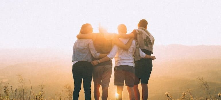 four friends looking at sunset before moving long distance