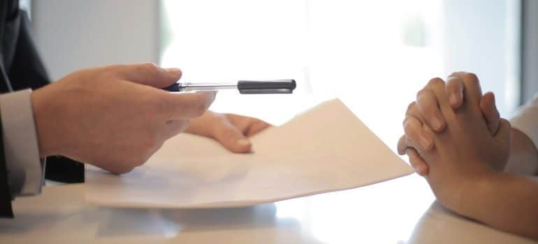 man giving a woman a pen and papers