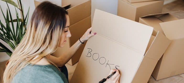 woman writing books on a box