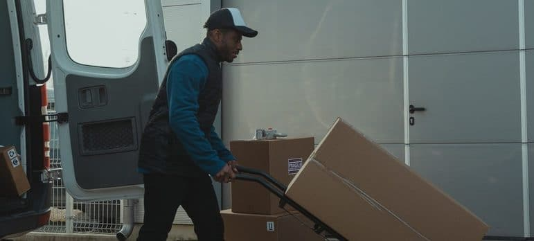 a guy using a dolly to move boxes