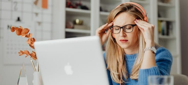 a stressed woman in front of a laptop