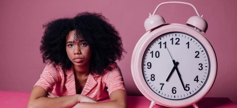 a woman next to a big pink clock