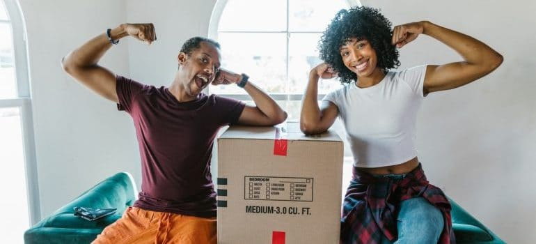 Two people flexing their muscles and smiling