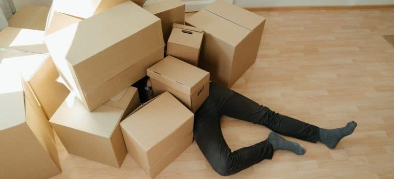 a person lying under the boxes